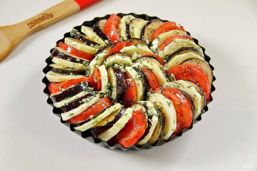 Сверху выложите овощи, чередуя их между собой. Смажьте овощи при помощи кулинарной кисти чесночной заправкой. Накройте форму фольгой и поставьте в разогретую до 200 градусов духовку примерно на 1 час.