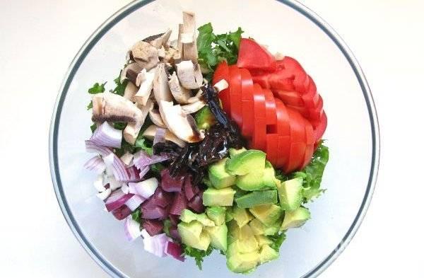 Все овощи хорошо вымоем, достанем мякоть из авокадо, нарежем дольками. Нарезаем помидор ломтиками, грибы чистим и режем пластинками, разрезаем оливки, салат рвем руками. Измельчаем луковицу (или ее часть, по вашему вкусу). Кладем все в салатницу.