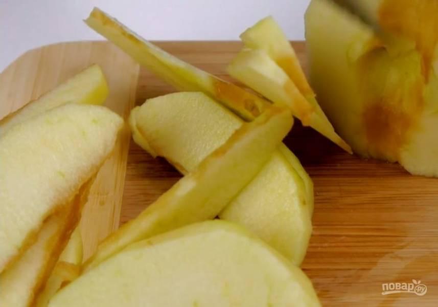 1. Дно формы выстелите бумагой для выпечки. Бортики смажьте тонким слоем сливочного масла и прикрепите полоски бумаги. Очищенные яблоки нарежьте дольками толщиной примерно полсантиметра.