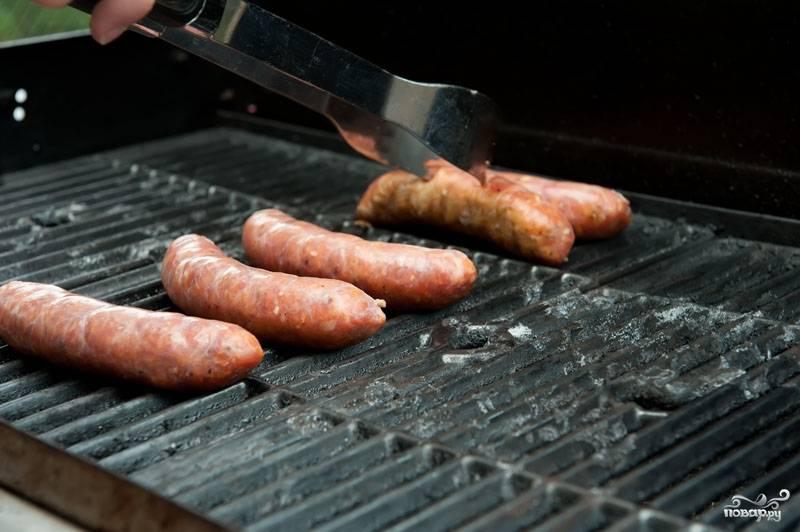 Сосиски выложите на гриль, готовьте на среднем огне, периодически переворачивая на протяжении 15-20 минут.