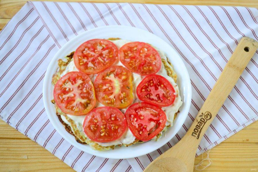 Разложите кружочки помидоров. Прослойку из помидоров можно делать не после каждого блина, а, например, через один, или вовсе сделать такую прослойку только раз, в середине.