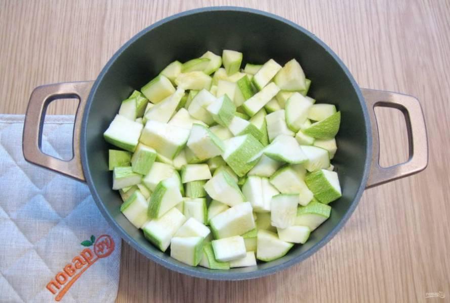 Кабачки помойте и очистите. Молодые с тонкой кожицей можно не чистить. Если в кабачках крупные семечки, то их нужно вырезать. Нарежьте кабачки кубиками, но не очень мелко. Выложите в кастрюлю к остальным овощам.