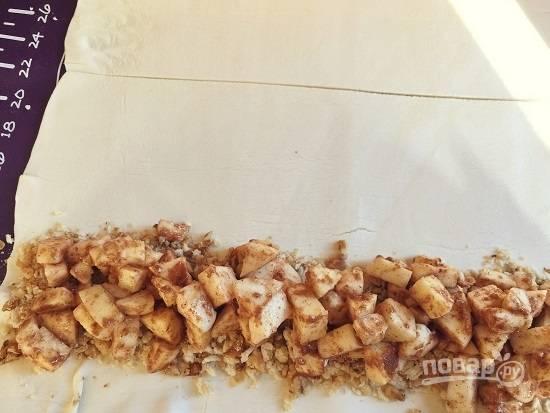 Высыпаем на один пласт теста, отступив от края примерно 4 см, половину смеси орехов и сухарей, а поверх выкладываем половину яблок. Второй штрудель делаем точно так же.