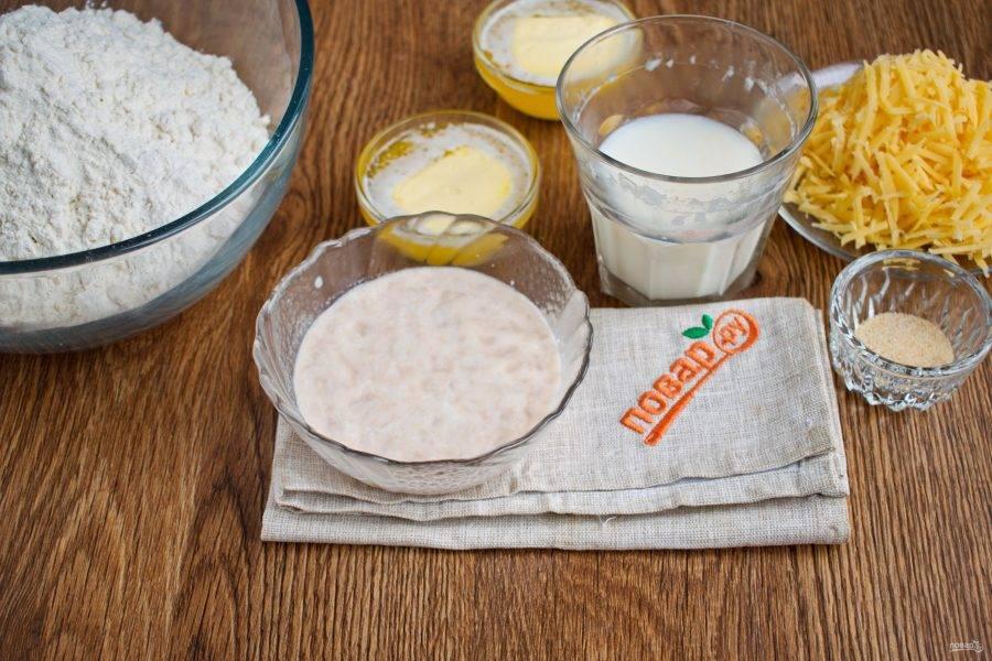 Масло растопите. Свежие дрожжи и сахар разведите в теплом молоке, поставьте в теплое место до появления пенной шапочки. Сыр натрите на терке.