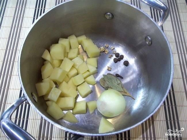 3. В кастрюлю выложите картофель, лук, лавровый лист и другие специи, которые вы будете использовать. Залейте все кипятком и поставьте на огонь. После закипания подсолите немного и варите на среднем огне около 10-13 минут.