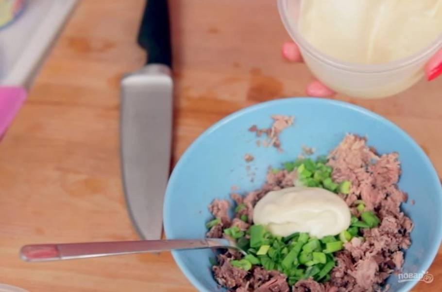 4. Приготовьте начинку: мякоть тунца немного раздавите вилкой. Добавьте к нему мелко нарезанный лук и майонез, перемешайте до однородного состояния.