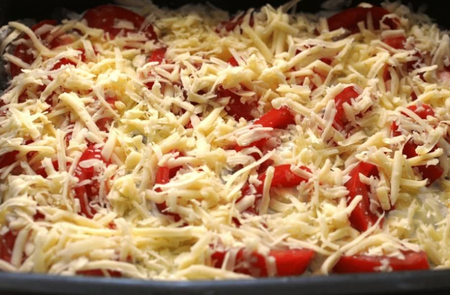 3. Достаем, выкладываем сверху лук полукольцами, кусочки помидоров и обильно посыпаем блюдо оставшимся тертым сыром. Отправим дальше запекаться до расплавленного состояния сыра.