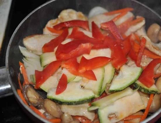 Затем добавьте лук и морковь, а через пару минут перец и цуккини. Перемешайте и жарьте 5 минут.