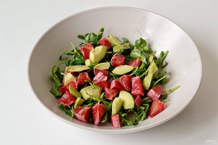 Затем добавьте авокадо и апельсин. Аккуратно перемешайте салат. Перед подачей посыпьте салат кунжутом.