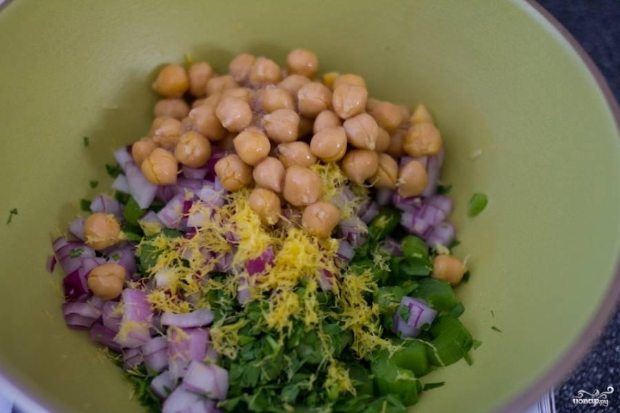 Две трети нута измельчите в блендере. Потом добавьте к нему оставшийся целый нут, мелко порезанный лук, зелень и цедру лимона.