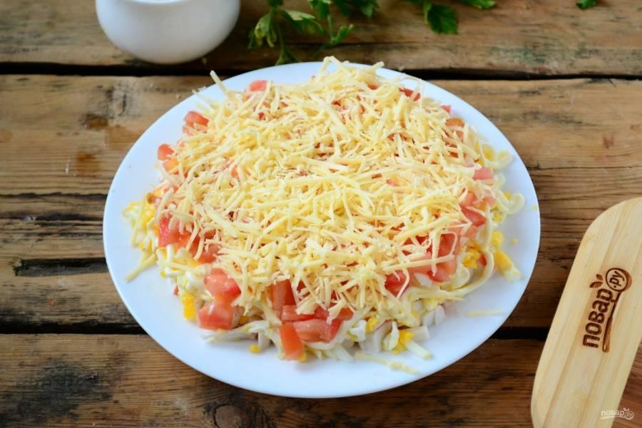 Твердый сыр натрите на мелкой терке, выложите его последним слоем на помидоры.