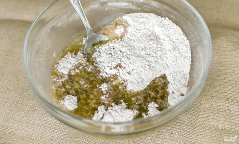 Затем масло с кипятком быстро добавьте в сухую смесь, замесите тесто.