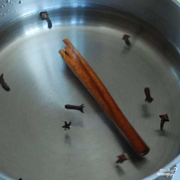 В небольшую кастрюльку наливаем воду, кладем палочку корицы и гвоздики.