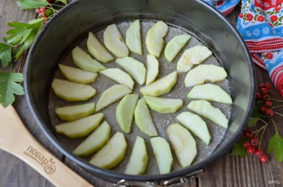 Форму застелите пергаментом, смажьте рафинированным маслом и присыпьте немного сахаром. Яблоки очистите от кожуры и сердцевины, порежьте дольками и уложите по кругу.