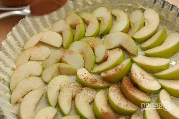 Яблоки очистите и нарежьте дольками, уложите красиво в форму, смазанную маслом и присыпанную манкой. Посыпьте яблоки корицей.