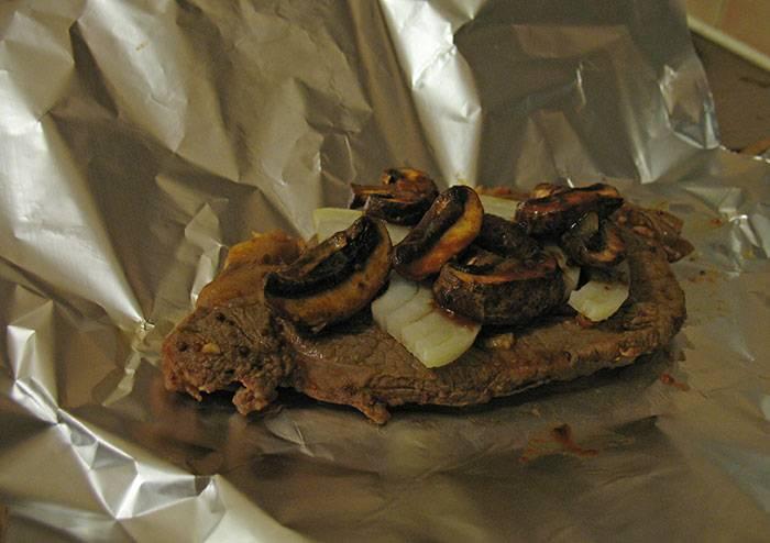 Разогрели духовку до 190 градусов. Обжарили в той же сковороде грибы, затем выложили их поверх лука, полили соусом со сковороды.