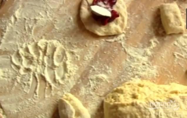 5. Вишню очистите от косточек. Каждую лепешку из теста приплюсните пальцами, в центр положите вишню и чайную ложку сахара. Аккуратно соедините края так, чтобы получился пирожок.