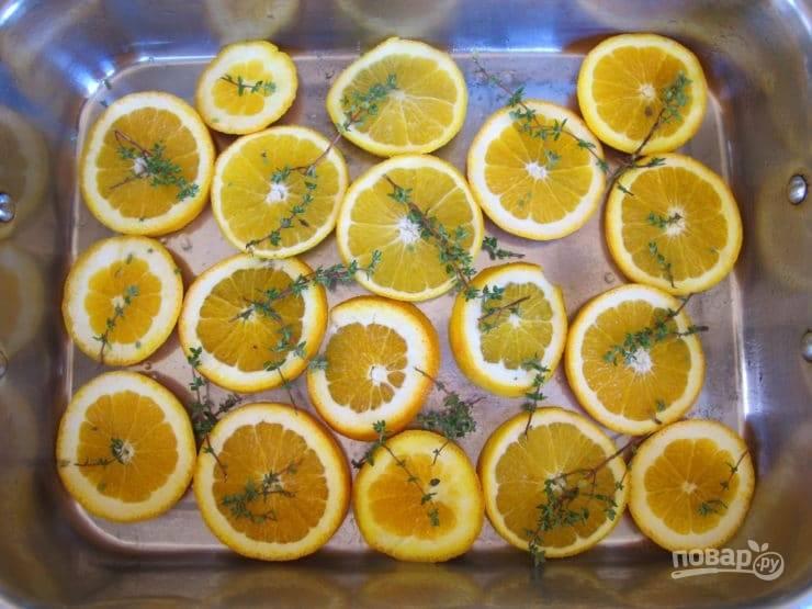 3. Затем нарежьте апельсин кружками. Выложите их в форму для выпечки. По фруктам разложите веточки тимьяна.