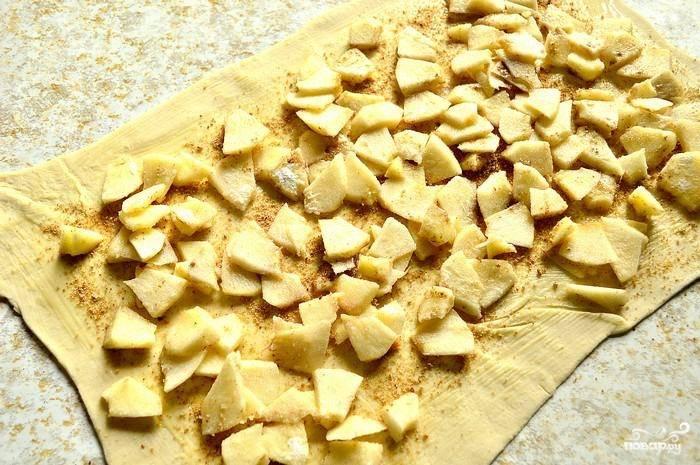 Разогрейте духовку до 180 градусов. Уложите яблочную начинку, сверните тесто в рулет. Сделайте надрезы на тесте.