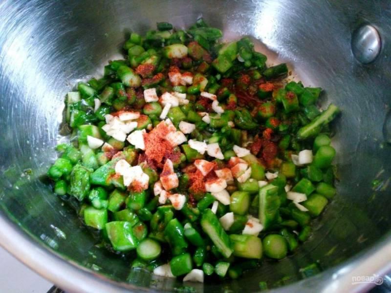Добавьте к спарже измельчённый чеснок и паприку (или другие специи), посолите по вкусу и перемешайте ингредиенты, готовьте ещё не более минуты, а затем снимите ковш с плиты.