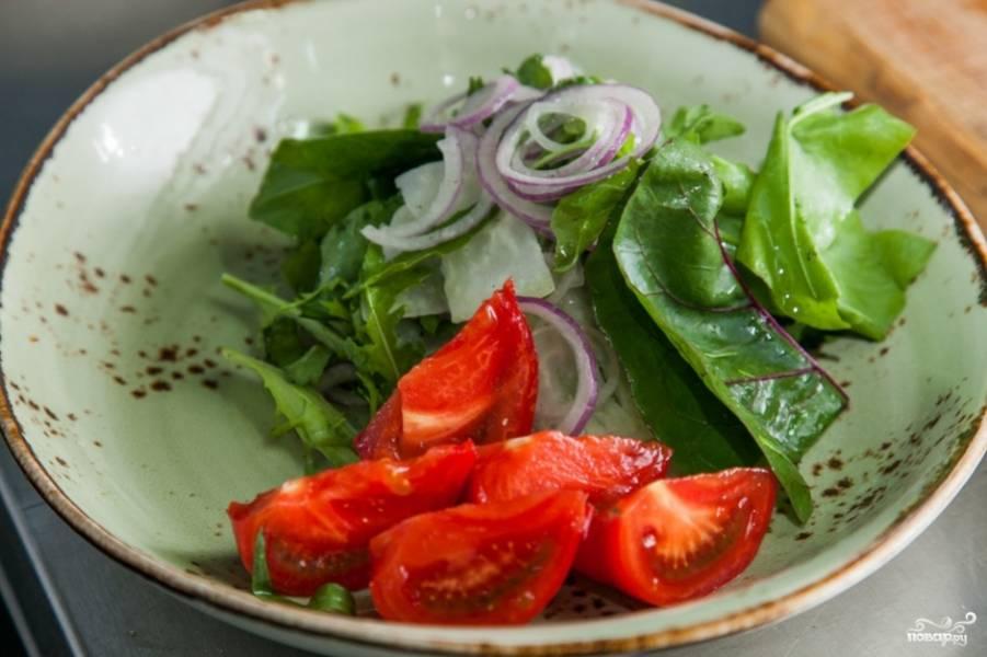 Так как сыр нужно подавать максимально горячим, пока отложим его в сторону, чтобы приготовить салат. Для этого возьмите салатные листья, вымойте их и порвите руками. Выложите на блюдо для подачи, добавьте нарезанные лук и помидоры. Сбрызнете все оливковым маслом, слегка подсолите, добавьте специи.