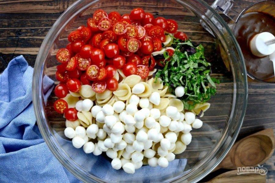 2. Когда паста остынет, соедините её в салатнице с маленькими шариками сыра и половинками помидор. Добавьте нарезанный базилик.