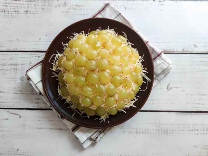 Виноград хорошо помойте, разрежьте пополам  и украсьте салат по всей поверхности.