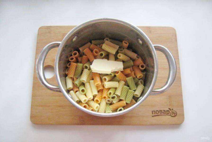 Пока фарш с луком жарится, отварите макароны. В кипящую, подсоленную воду выложите макароны и варите по инструкции на упаковке. Мне на это потребовалось 15 минут. После воду слейте, а макароны верните в кастрюлю. Добавьте сливочное масло и перемешайте.