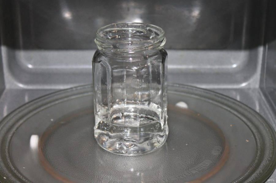 Тщательно вымойте банки с пищевой содой и горячей водой. Налейте в банки воду высотой в один сантиметр. Поставьте в микроволновую печь и стерилизуйте на мощности 800 Ватт в течение 4 минут. Железные крышки прокипятите в течение 10 минут.