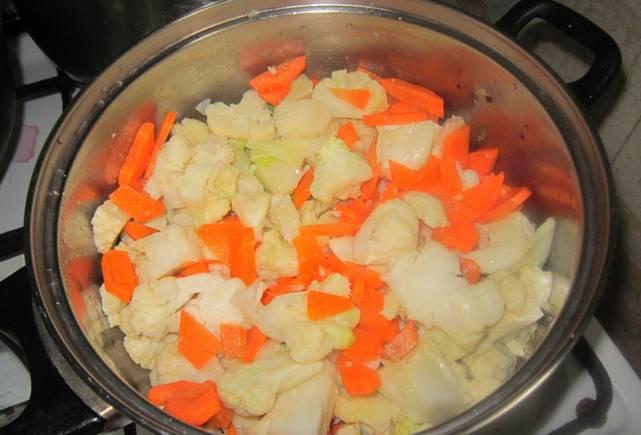 Цветную капусту отварите до готовности, опустив ее в кипящую, подсоленную воду на 3-4 минуты. Разберите капусту на соцветия и поместите в кастрюлю с растительным маслом. Также добавьте измельченную морковь, лук и сладкий перец. Тушите на медленном огне 15 минут.