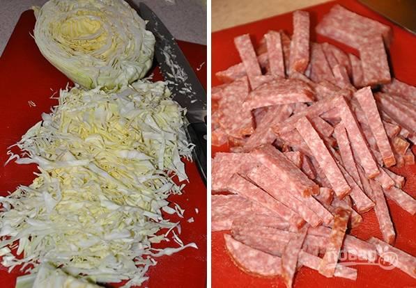 2. Капусту мелко нашинкуйте и выложите в глубокий салатник. Нарежьте тонкой соломкой копченую колбаску.