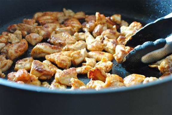 2. На сковороду налить растительное масло и разогреть его. В горячее масло отправить курицу и обжарить каждый кусочек с двух сторон до золотистой корочки.