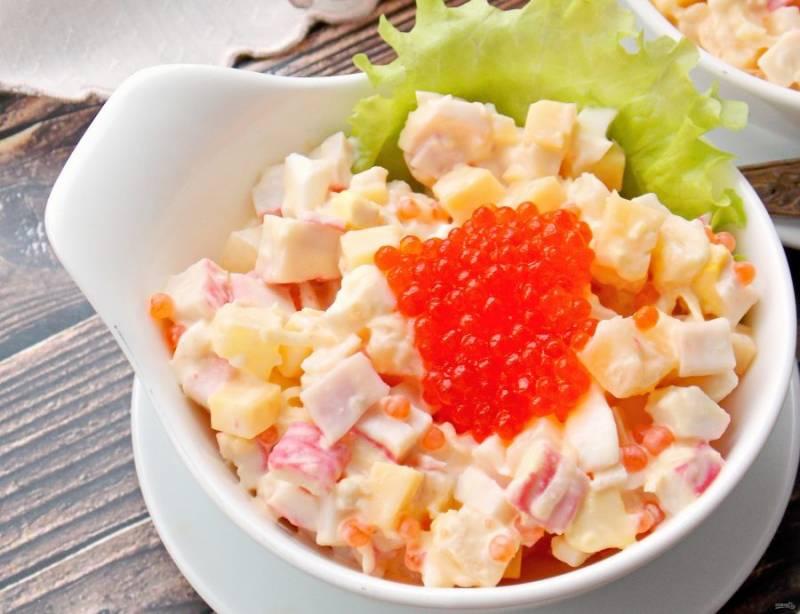 В салатник уложите листья салата, сверху выложите крабовый салат. Украсьте верх оставшейся икрой.