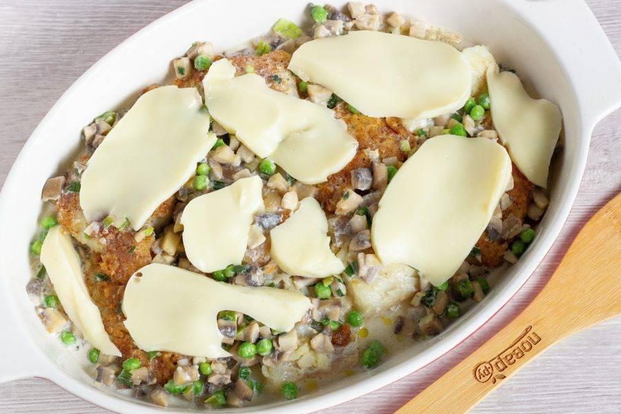 Залейте рыбу сливочно-овощной массой и выложите сверху нарезанный сыр. Поставьте в разогретую до 180 градусов духовку на 15-20 минут.