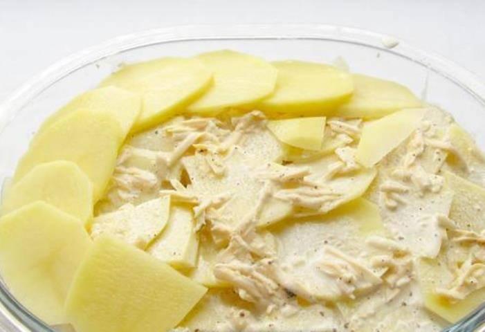 Полейте этой заливкой первый слой картофеля и выложите второй слой.