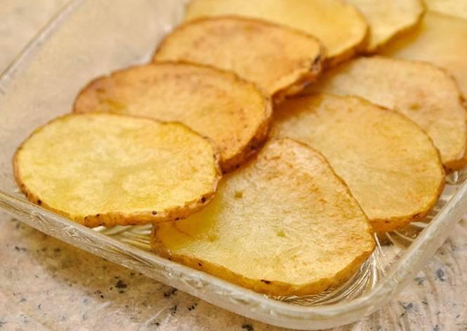 6. Готовые картофельные чипсы посыпьте любимыми специями или солью (если вы картофель не замачивали) и подавайте. Приятного аппетита!