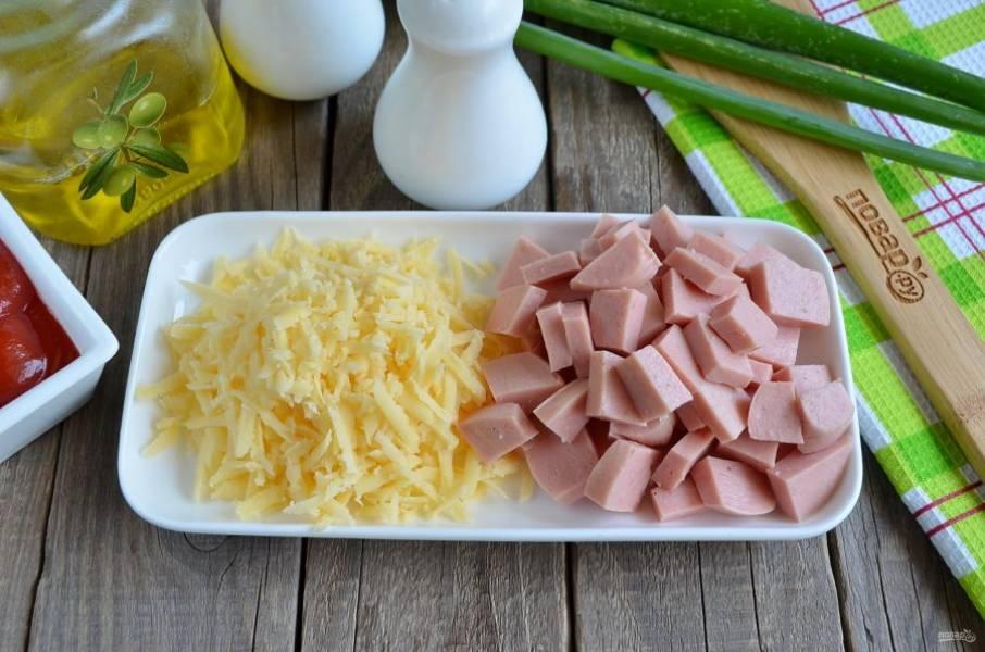 Пока картофель в духовке, можно подготовить начинку. Порежьте колбасу небольшими кусочками, сыр натрите на крупной терке.