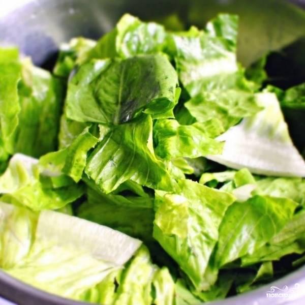 Тем временем выкладываем в салатницу крупно нарезанные листья салата.