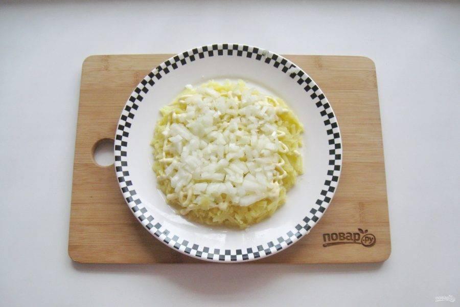 Репчатый лук очистите, помойте и мелко нарежьте. Обдайте кипятком, чтобы лук отдал горечь. Выложите лук на картофель.