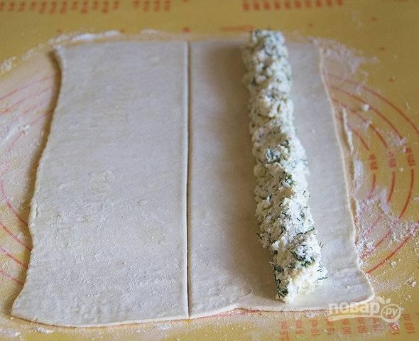 3. Раскатайте слоеное тесто на рабочем столе. Выложите начинку, аккуратно сверните рулетом.