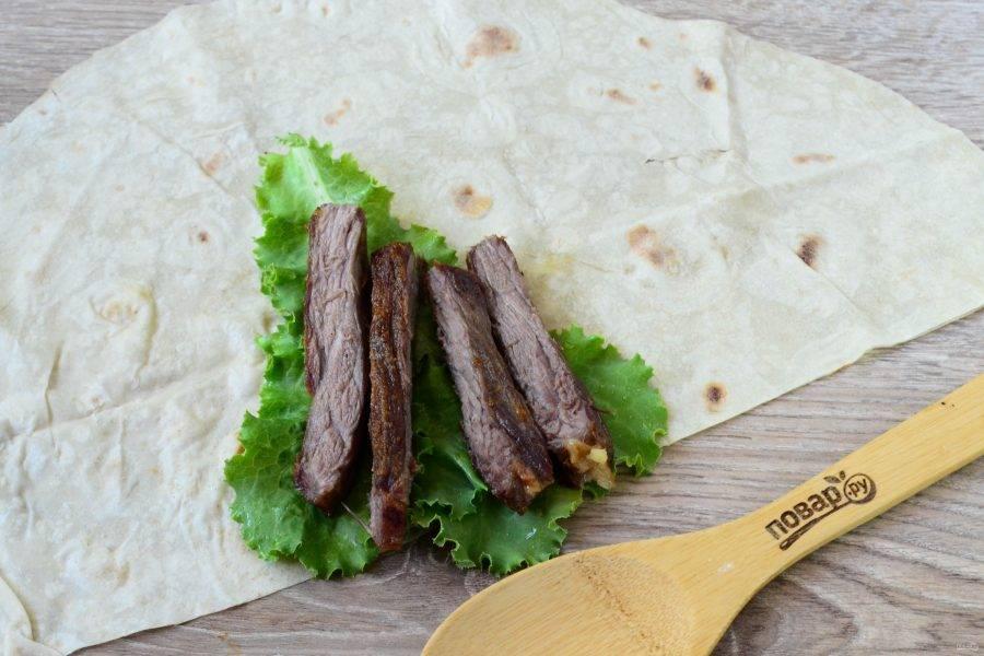 Круглый лист лаваша разрежьте пополам. На край одной половины положите листья салата, а сверху – порезанную соломкой говядину.