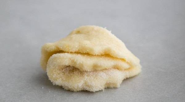 9. Если песочное печенье с творогом в домашних условиях все-таки будет с сахаром, то кусочек теста нужно опустить в тарелку с сахаром, а затем свернуть (так, чтобы сахар оказался внутри).