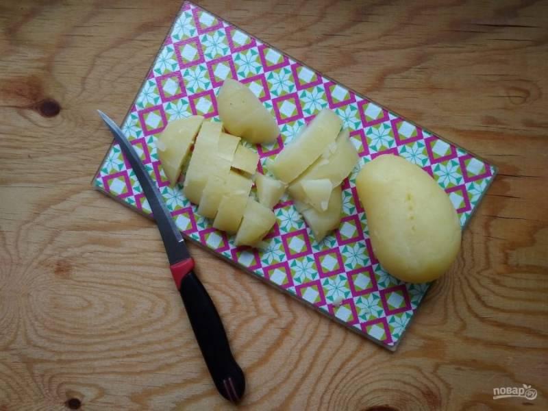 2. Заранее отварите до готовности промытый картофель в мундире. Затем остудите его, почистите и нарежьте.