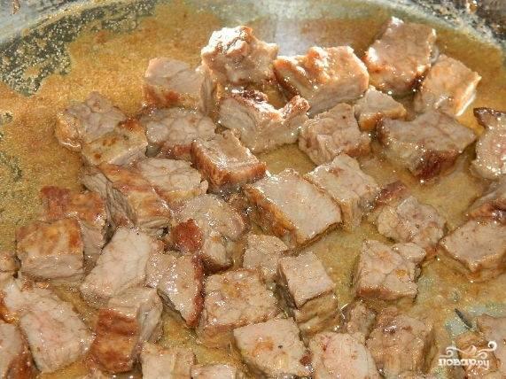 4.Раскалите сковороду, налейте растительное масло. Свинину нарежьте кубиками. Жарьте до готовности. Посолите, поперчите, добавьте выдавленный через пресс чеснок.