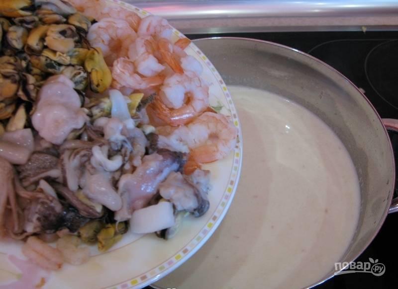 Всыпьте в суп морепродукты. Варите их в течение 10 минут на среднем огне.