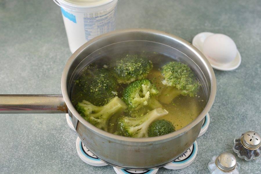 Вскипятите в сотейнике воду, чуть посолите, выложите в нее соцветия брокколи и отварите около 4 минут. Откиньте капусту на дуршлаг и дайте полностью стечь воде.