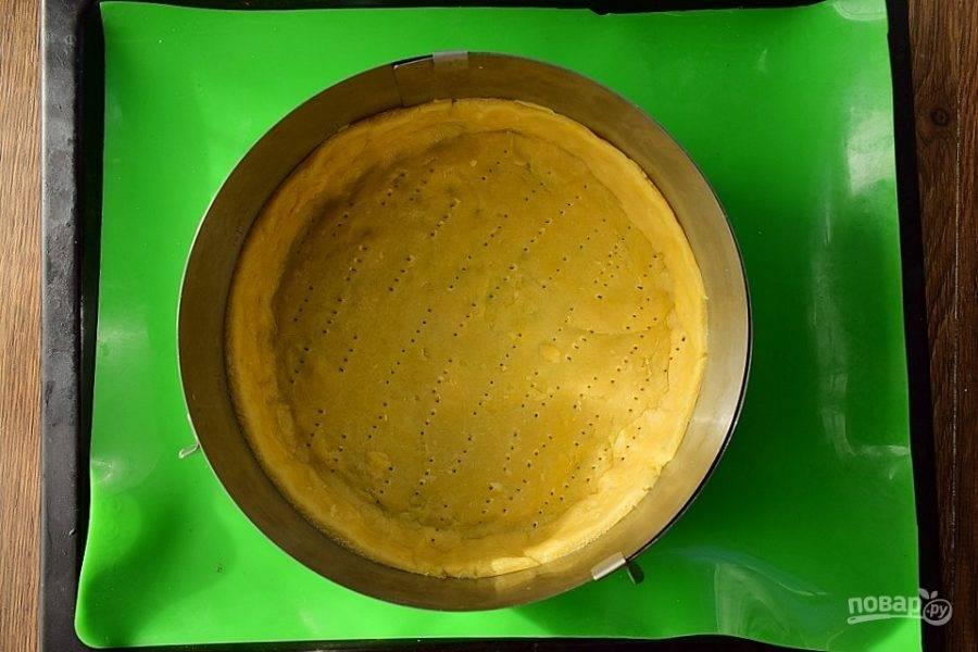 Тесто распределите руками  по форме для запекания (у меня разъемное кольцо, d - 24 см), сформируйте бортики. Наколите тесто  вилкой, поставьте в разогретую до 180 °С духовку на 15 минут.