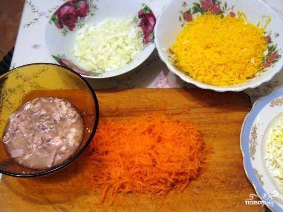 3.Куриные яйца сварите вкрутую. Остудите их в холодной воде. Очистите от кожуры, натрите на крупной терке. Натрите на терке морковь. Мелко подробите лук.