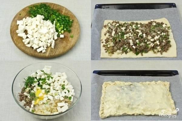 2.Брынзу нарежьте мелкими кубиками. Зелень мелко порубите. К фаршу добавьте жареный лук, нарубленную зелень и брынзу, вбейте яйца, поперчите и посолите по вкусу. Хорошо перемешайте. На противень положите пекарскую бумагу. Половину готового слоеного теста раскатайте и переложите на бумагу, выложите на него начинку. Сверху накройте второй частью теста, также раскатанной в тонкий пласт. Накройте пирог листом из теста. Поверхность смажьте оливковым маслом и проколите в нескольких местах, например — вилкой.