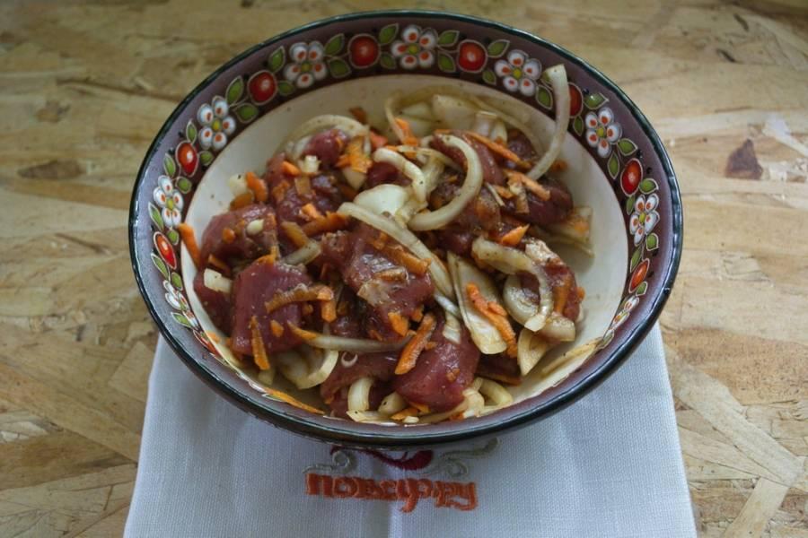 К мясу добавьте соль, специи, 2-3 ст. ложки растительного масла, морковь и нарезанный лук. Перемешайте.